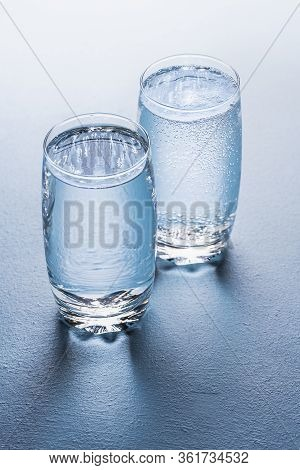 Two Water Glasses On A Blue Background, One With Plain Water And One With Tonic Water. Mineral Water