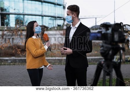 Young Journalist And Businessman With Medical Masks Outdoors. Virus Protection