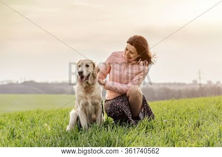 Happy woman petting adorable dog outdoors on field