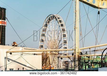 View Of The Ferris Wheel Through The Ship On The Embankment Of The Motlawa River In The City Of Gdan