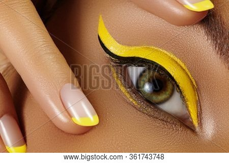 Close-up Female Eye With Bright Yellow Eyeliner Makeup. Neon Disco Make-up And Fashion Manicure. Sum