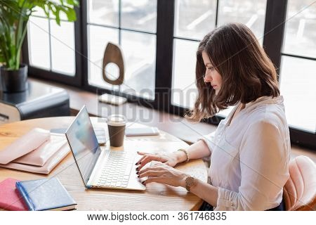 Business Woman In White Shirt Working At Laptop At Home Office, Drinking Coffee. Distance Learning.c