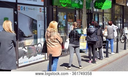 Warsaw, Poland. 17 April 2020. People Waiting In Line In Front Of A Supermarket At A Safe Social Dis