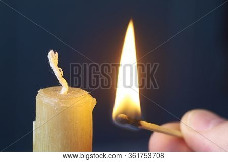 Close-up Male Hand Holds Burning Match And Lights Yellow Candle On Dark Background, Selective Focus