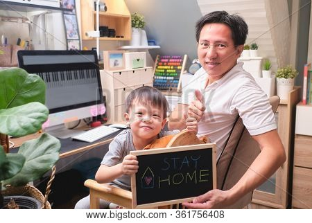 Stay Home Stay Safe, Cute Asian Kindergarten Boy And His Working At Home Father Are Holding Black Bo