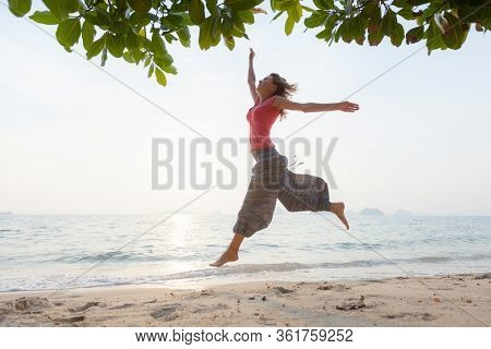 Young woman in hippie pants runs and jumps on the sandy tropical beach