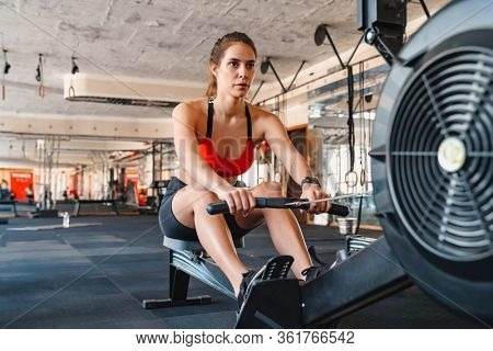 Confident young attractive sportswoman exercising on a rowing machine at the gym