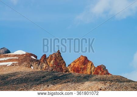 Awesome Sunny Mountain With Red Orange Brown Crags In Top Under Blue Sky. Colorful Stony Hill With S