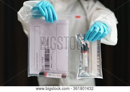Coronavirus Testing Process, A Hand Holds Tube Of Blood Test Samples And Swab Collection Kit Specime