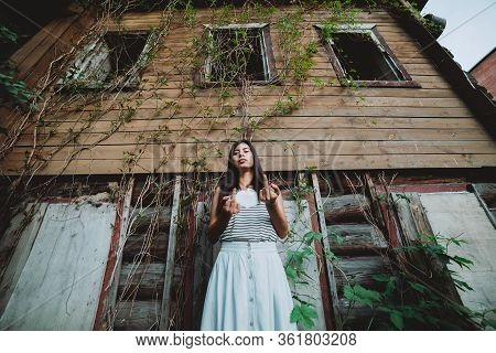 Crazy Girl Shows Middle Finger. Beautiful Mad Country Girl Near Old Rustic House With Broken Windows