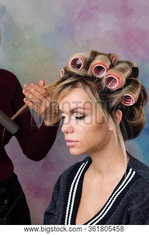 Process Of Creating Stylish Look Of Seductive Housewife. Portrait Of Beautiful Woman In Curlers. Mod