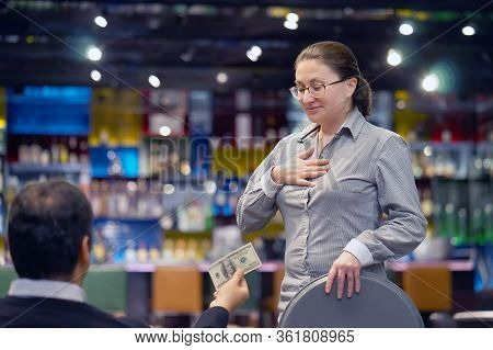 Waitress Takes The Tip. The Waiter Girl Receives A Tip From The Client At The Hotel Bar. A Bartender