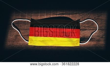 Germany National Flag At Medical, Surgical, Protection Mask On Black Wooden Background. Coronavirus