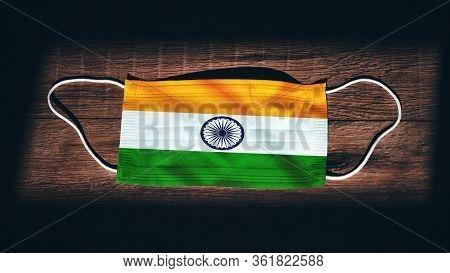 India National Flag At Medical, Surgical, Protection Mask On Black Wooden Background. Coronavirus Co