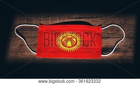 Kyrgyzstan National Flag At Medical, Surgical, Protection Mask On Black Wooden Background. Coronavir