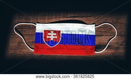 Slovakia National Flag At Medical, Surgical, Protection Mask On Black Wooden Background. Coronavirus