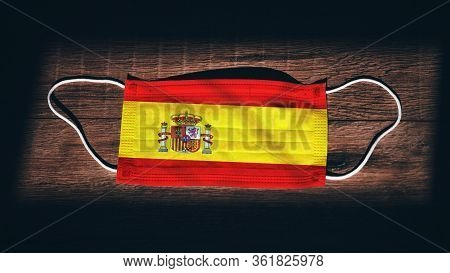 Spain National Flag At Medical, Surgical, Protection Mask On Black Wooden Background. Coronavirus Co