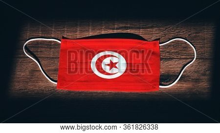 Tunisia National Flag At Medical, Surgical, Protection Mask On Black Wooden Background. Coronavirus