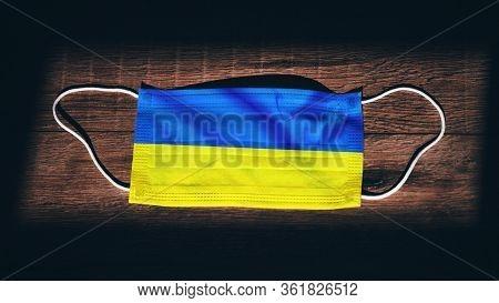 Ukraine National Flag At Medical, Surgical, Protection Mask On Black Wooden Background. Coronavirus