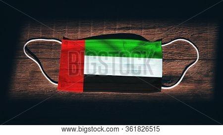 United Arab Emirates National Flag At Medical, Surgical, Protection Mask On Black Wooden Background.