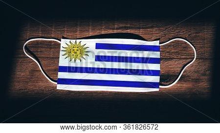 Uruguay National Flag At Medical, Surgical, Protection Mask On Black Wooden Background. Coronavirus