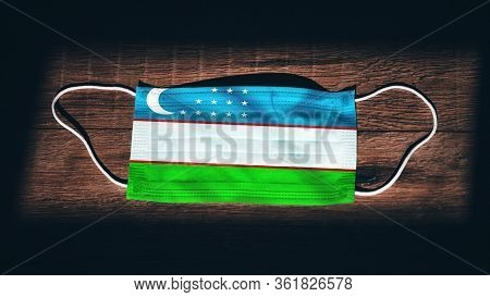 Uzbekistan National Flag At Medical, Surgical, Protection Mask On Black Wooden Background. Coronavir