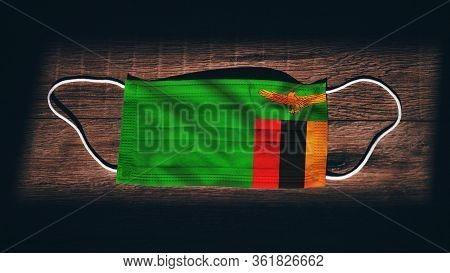 Zambia National Flag At Medical, Surgical, Protection Mask On Black Wooden Background. Coronavirus C