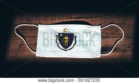 Massachusetts Flag. Coronavirus Covid 19 In U.s. State. Medical Mask Isolate On A Black Background.