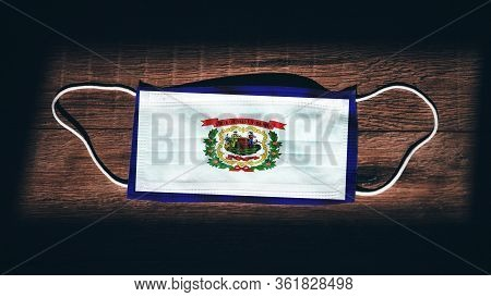 West Virginia Flag. Coronavirus Covid 19 In U.s. State. Medical Mask Isolate On A Black Background.