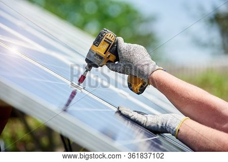 Close Up View Of Technician Working With Screwdriver Installing Solar Photo Voltaic Panel To Metal P