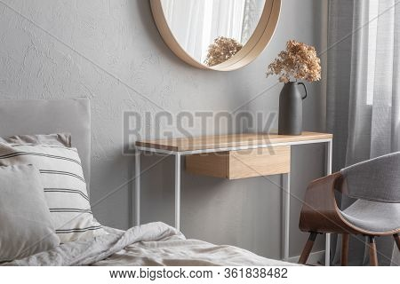 Elegant Round Mirror In Wooden Frame Above Fancy Console Table With Flowers In Vase In Trendy Bedroo