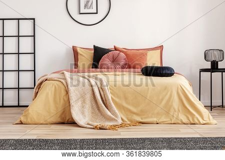 Black Round Velvet Pillow On Yellow Duvet In Trendy Bedroom Interior With King Size Bed