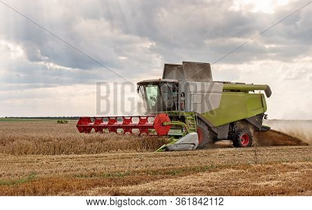 Combine Harvester In Action On Wheat Field.