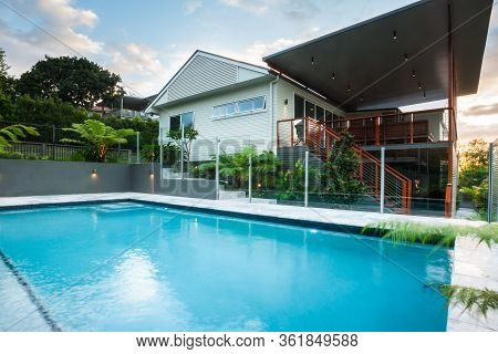 Luxury Poolside Closes Up With Modern House With Green Trees Under A Blue Sky With Clouds, There Is