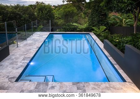 Luxury Swimming Pool Closeup With Blue Water Next To Green Forest Around In A Dark Environment, The
