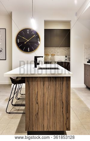 Modern Kitchen Countertop Made In Wood With A Wall Watch And Chairs Of A Luxury House