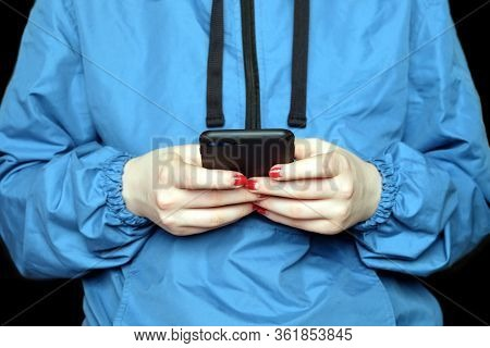 Young Girl Wearing In Blue Windbreaker Looks To The Screen Of Black Smartphone Photo On Black Backgr