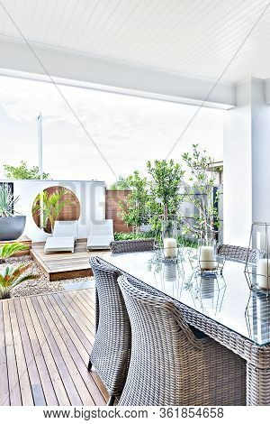 Outdoor Patio Area With Rattan Chairs On The Wooden Floor Next To The Glass Panel Table, There Are C