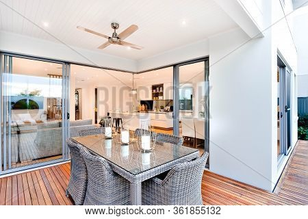 Outdoor Patio Area With Table Set Up Beside An Entrance To Inside Of A Modern House With A Kitchen,
