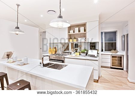 House Interior With Kitchen Decorations Including Lights And Counter Close Up Beside The Silver Stov