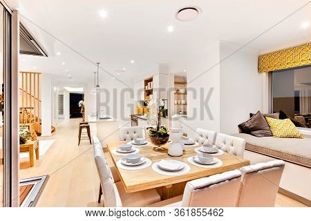 Modern Dining Set Up With Wooden Table In The Living Room Near To The Relaxing Area With Pillows And