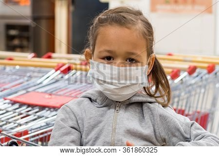 Portrait Of Little Child Girl In Medical Mask Is Gazing At Camera In Supermarket. Virus Epidemic Con