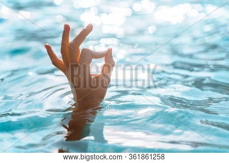Woman Hand Make A Sign, Ok On The Background Of Azure Sea Water And The Glare Of The Sun. Female Han