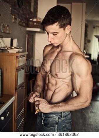 Shirtless Muscular Young Man Eating Cereal Bar, Looking At Camera Standing,