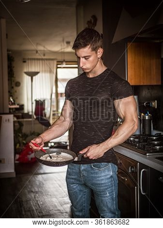 Male Bodybuilder Cooking In Kitchen At Home