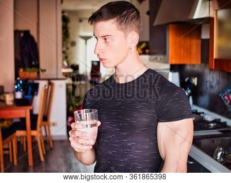 Young Man In Kitchen Drinking Water From A Glass