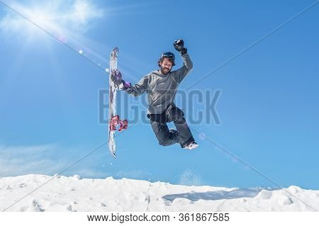 Snowboarder Make Fun And Jump With Snowboard In His Hand