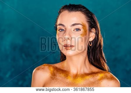 Perfect Naked Girl Covered With Gold Paint And Shimmering Sparkles On Green Wall In Studio. Glowing