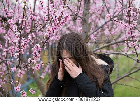 Pretty Girl Sneezing Beside Blooming Tree. Spring Allergy Concept