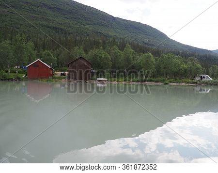Shore At Svartisvatnet Lake And Mountains Reflected In Water Near European Svartisen Glacier In Nord